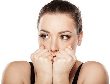 frightened young woman covering her mouth with her hands