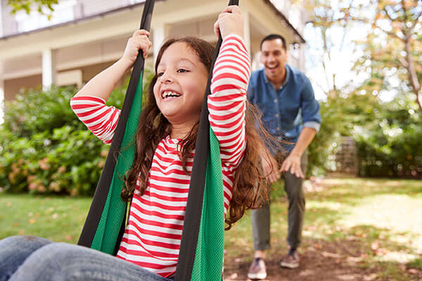 Father pushing daughter on a swing in a pest free yard | Prime Pest Solutions